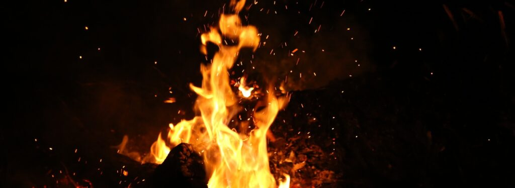 Picture of a big outdoor fire in the dark of night.