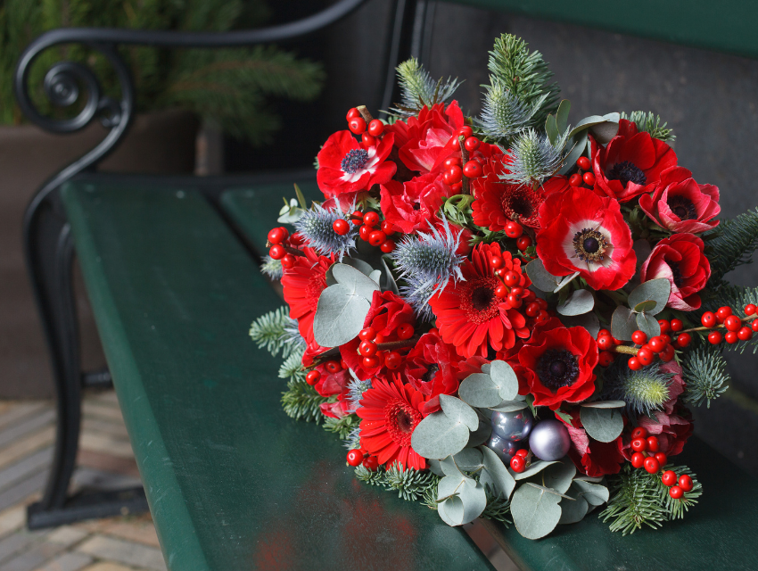 Lakeside-Living_Manitowish-Waters-WI_How-to-Show-Your-Loved-Ones-You-Care-This-Holiday-Season_Bouquet-of-Holiday-Flowers-on-Green-Bench