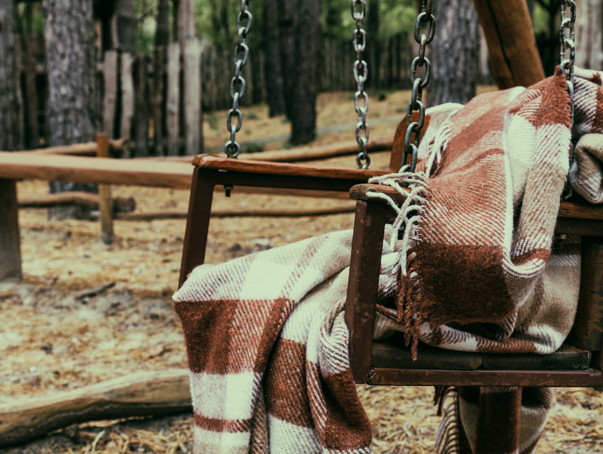 Lakeside-Living_Manitowish-Waters-WI_How-to-Show-Your-Loved-Ones-You-Care-This-Holiday-Season_Cozy-Blanket-on-Outdoor-Swing-in-the-Woods