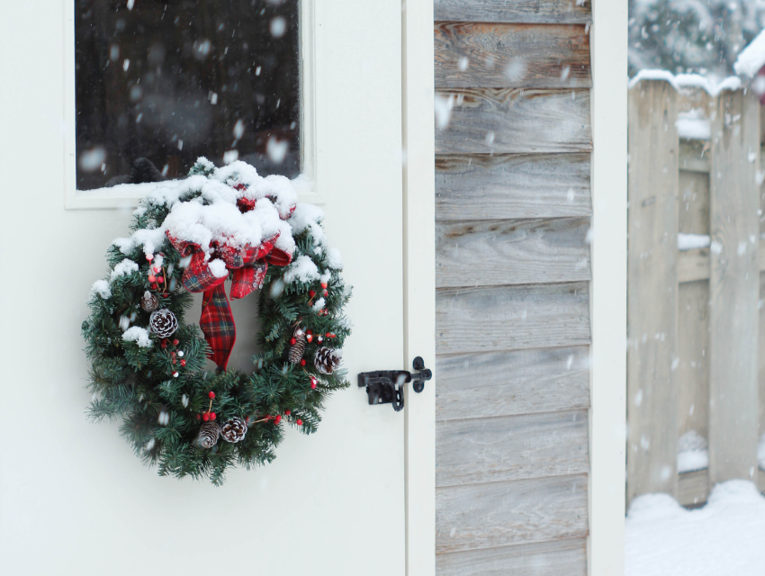 Lakeside-Living_Manitowish-Waters-WI_How-to-Show-Your-Loved-Ones-You-Care-This-Holiday-Season_Wreath-on-White-Door-to-Cabin-in-the-Winter