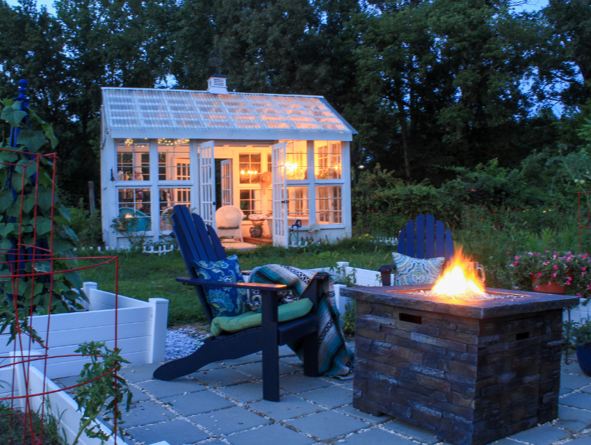 Lakeside-Living_Manitowish-Waters-Wisconsin_Northwoods-Interior-Design-outdoor-fire-table-selection-backyard-fire-table-adirondack-chairs-white-decorative-green-house