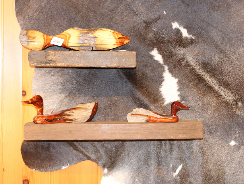 lakeside-living-design-northwoods-wi-cabin-decor-live-edge-floating-shelves-displaying-wood-fish-ducks