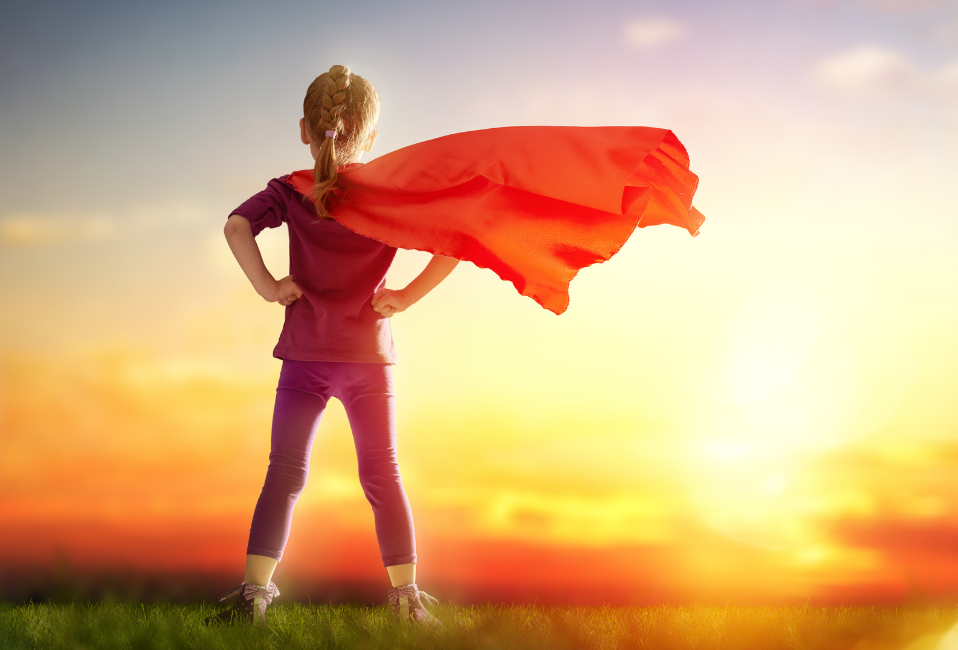 Girl with red cape looking at sunrise