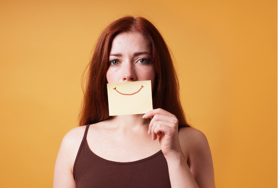 woman holding yellow sticky to face with red smile drawn on