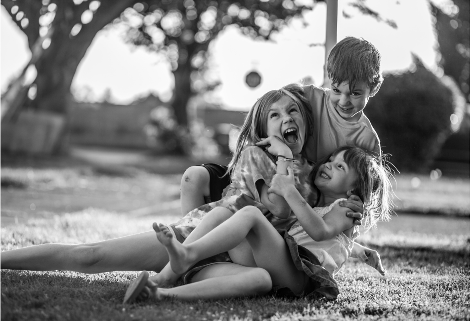 black and white picture of three children playing/wrestling