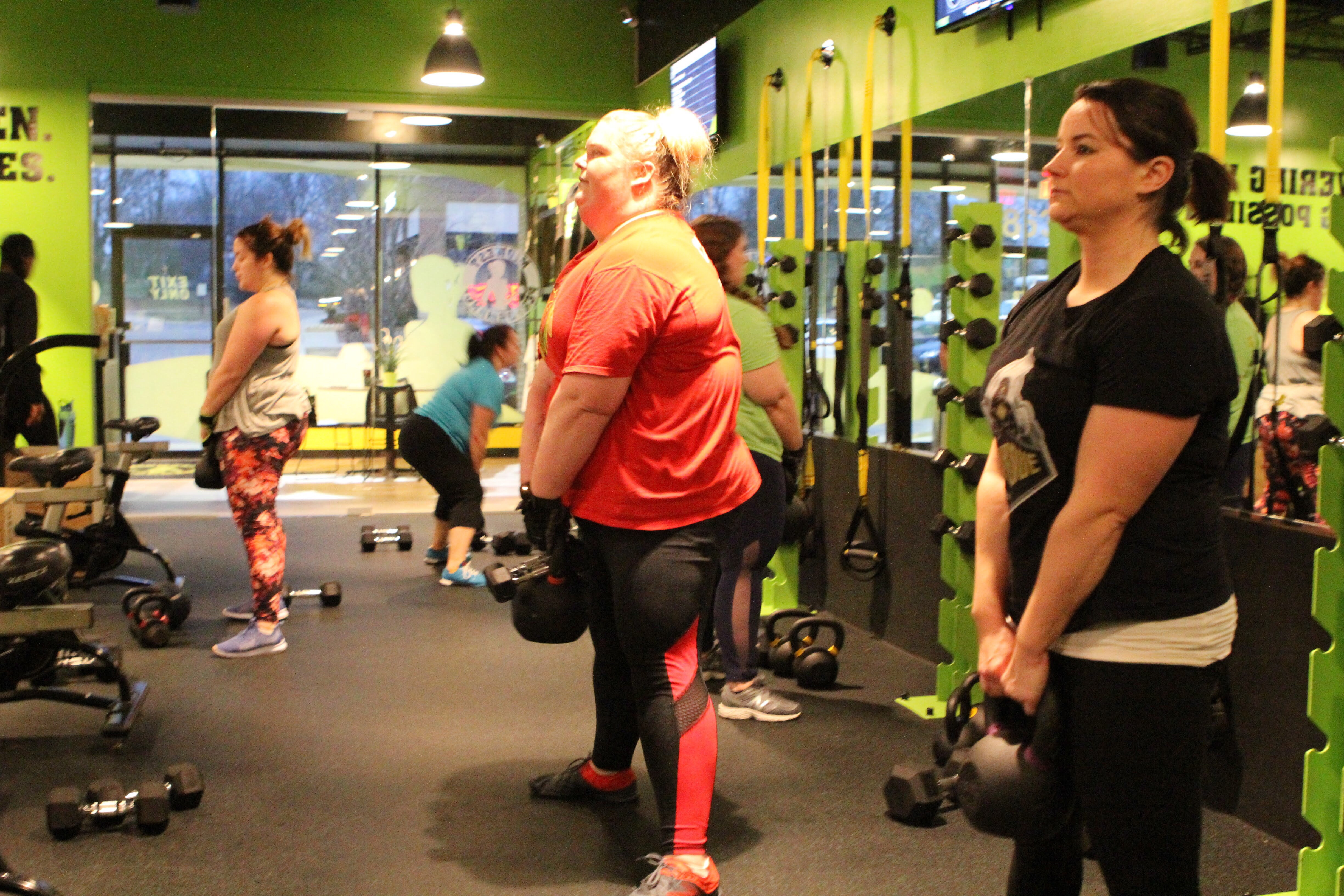 group women watching one woman lifting weights