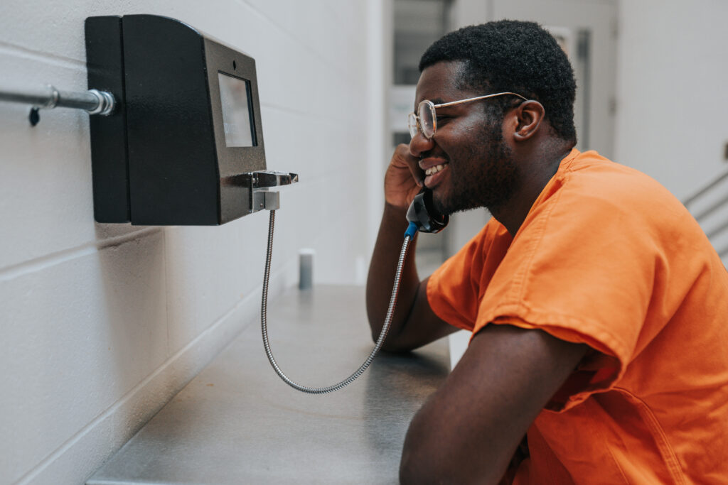 Inmate smiling while talking on a CIDNET Inmate Kiosk