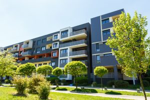 Exterior of a modern black apartment buildings on a blue sky background. No people. Real estate business concept.