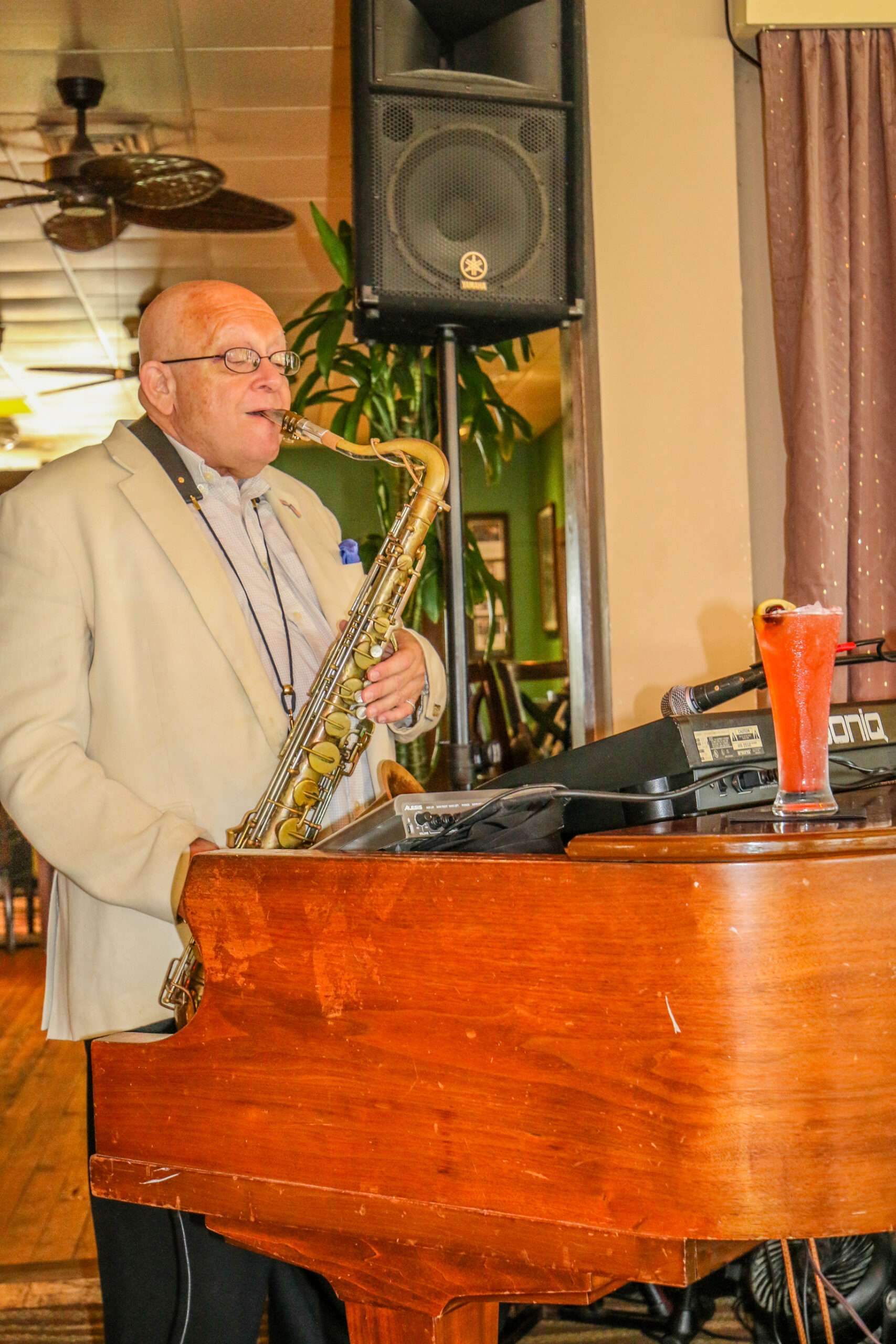 MAN PLAYING SAXAPHONE IN FRONT OF A PIANO