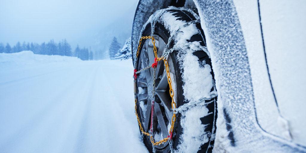 car with tire chains driving through deep snow