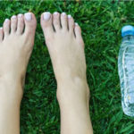bare feet and a water bolle on grass