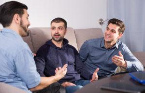 male friends enjoying сonversation on sofa at home