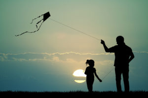Father guiding kit with daughter