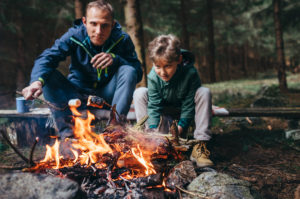 Father and son roast the marshmallows on the camp fire