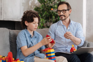 serious boy assembling erector set with his father on couch