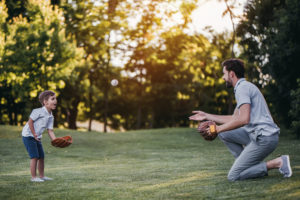 dad and son playing catch in a field
