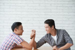teenage boy arm wrestling with his father