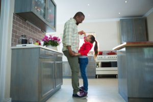 father daughter dancing in kitchen
