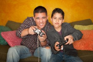 Hispanic father and son playing video games