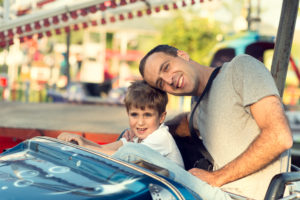 father and son riding in a bumper car