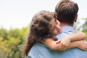 girl embracing her father outdoor.
