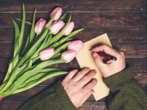 Man hands writing on blank paper on old wooden table bunch of flowers on the table