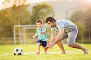 father son playing soccer in field