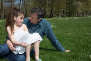 father and daughter talking in park