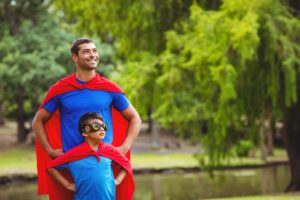 Father and on dressed up as Super hero out with hands on hips.