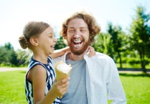 Laughing girl with ice-cream and her father having fun in park at leisure