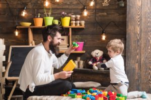 Dad and child play with toy cars, bricks. Nursery with toys and chalkboard.