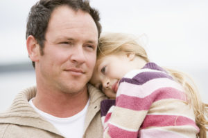 Father hold daughter resting on his shoulder