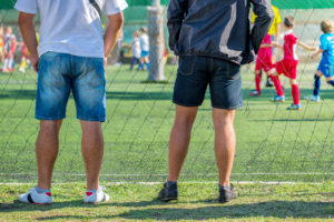 Fathers watching their sons playing soccer game.