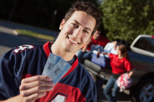 Man showing off football tickets.