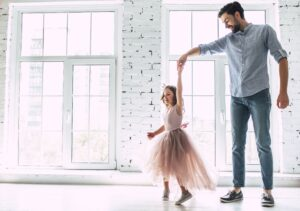 Father spinning daughter and dancing