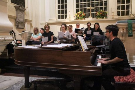 Choir group rehearsing with piano