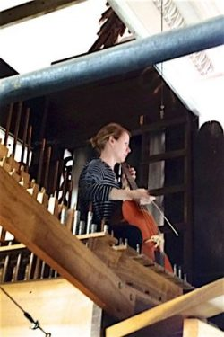 A gamba player tests acoustics in the organ case.