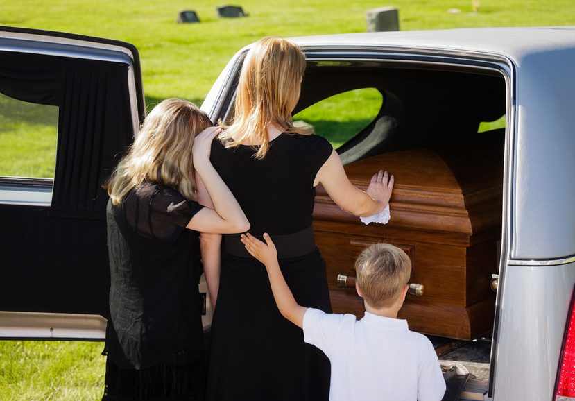 A woman and two children standing behind an open hearse.