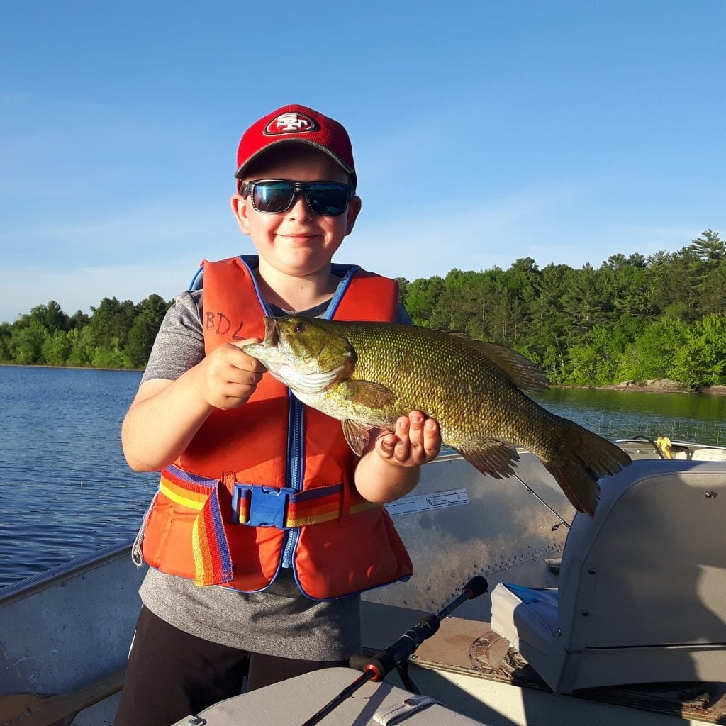 Young boy holding a French River Smallmouth Bass