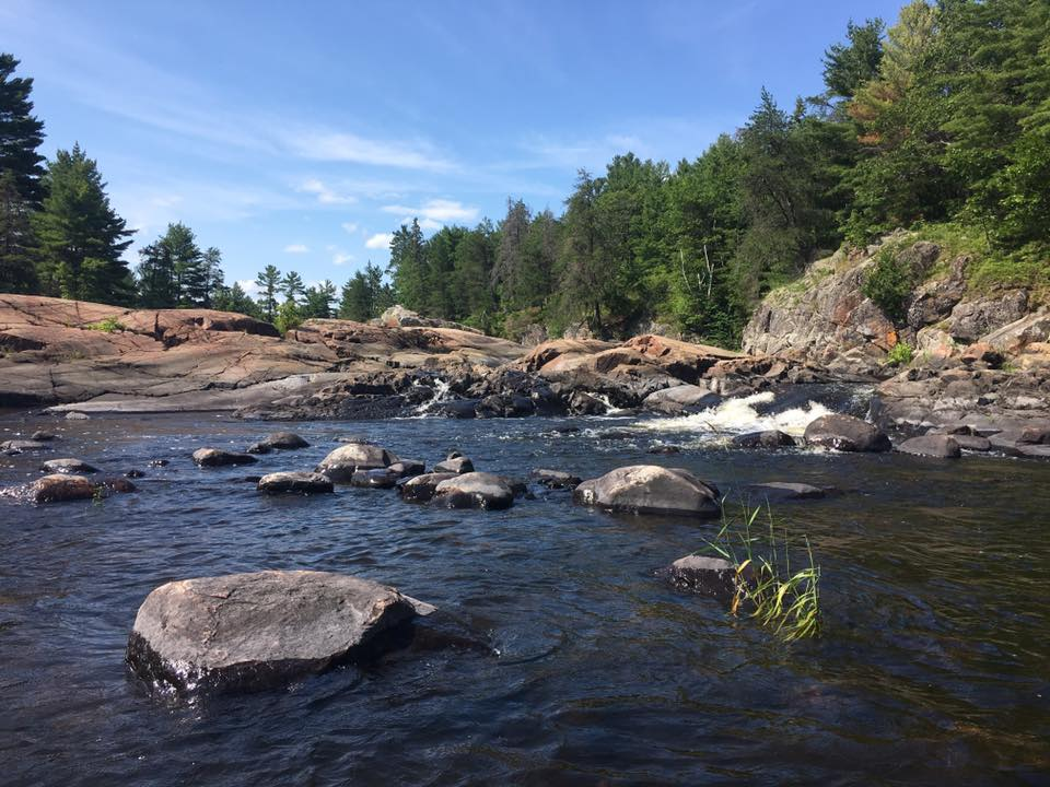 Scenery photo displaying the upper end of the Sturgeon Chutes in the Northern part of the Lower French River Provincial Park, Northeastern Ontario Canada. The image displays rocky granite structure, green vegetation, Pine trees, and a small waterfall.
