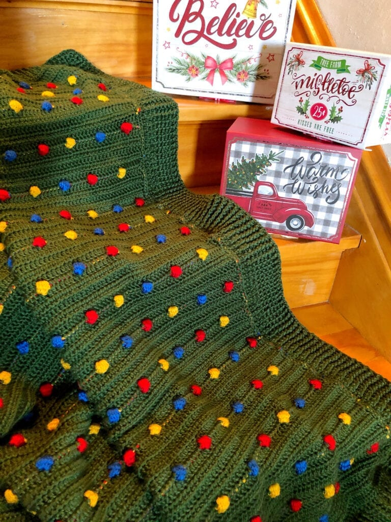 Festive Light Crochet Blanket on Steps with Holiday Boxes Decorated