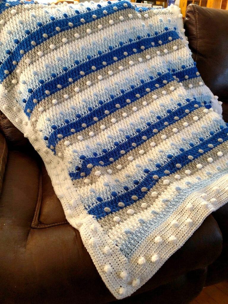 Crochet Blue, White, Silver Christmas Blanket on Sofa