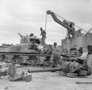 A 75mm gun being salvaged from a knocked-out Sherman tank at 26th Armoured Brigade workshops in Perugia, 30 June 1944. The entry point for an 88mm shell can be seen on the side of the tank's hull. © IWM (NA 16518)