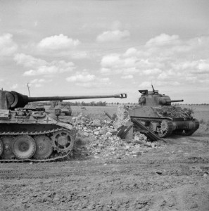 A Sherman tank of 24th Lancers, 8th Armoured Brigade, passing a knocked-out German PzKpfw V Panther tank near Rauray, 30 June 1944. © IWM (B 6226)