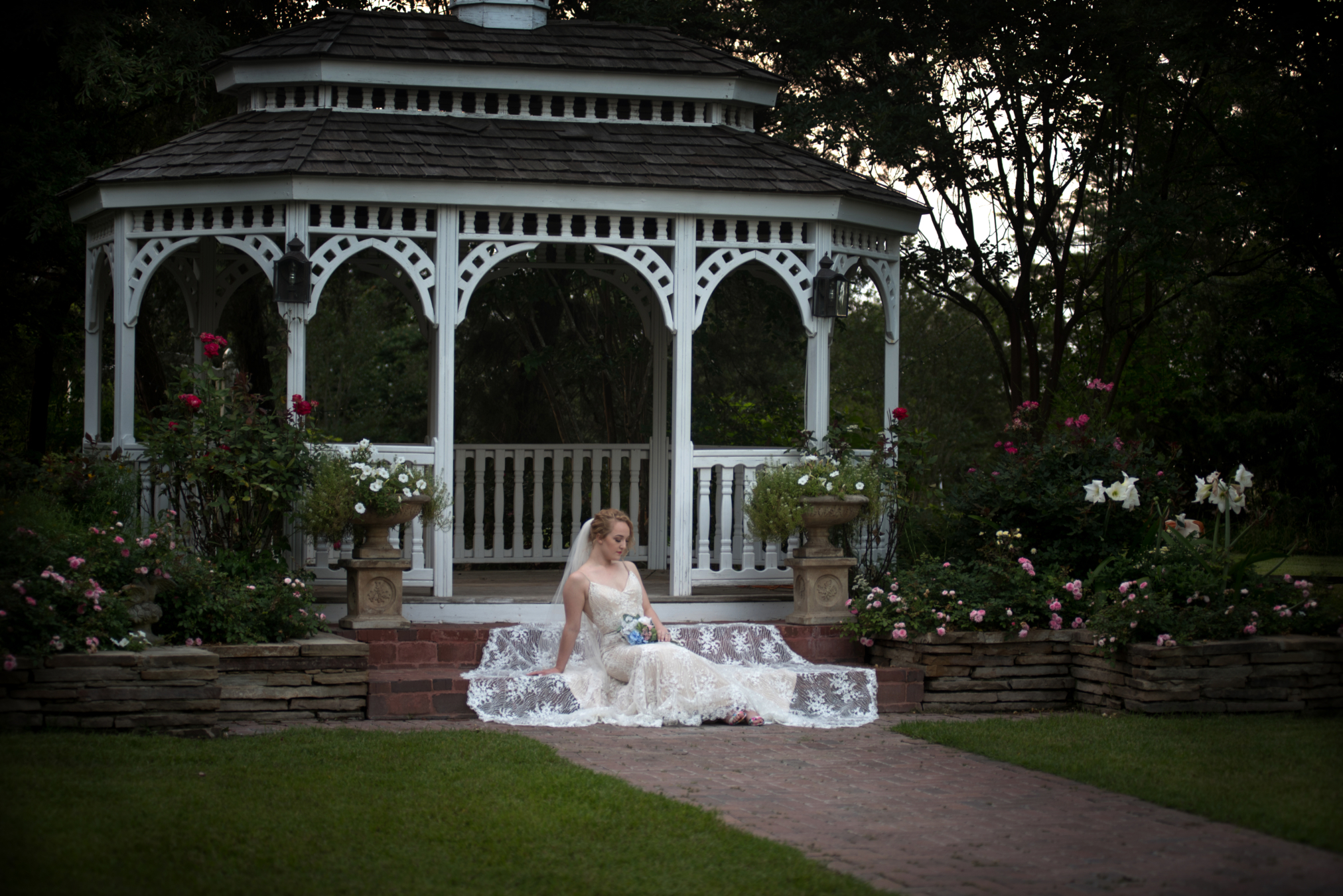 Portrait of a bride sitting on the steps of a gazebo at dusk - Covid-19 Weddings