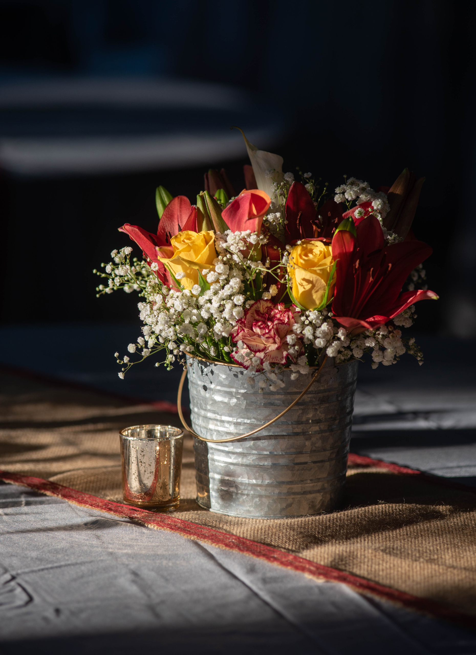 yellow and tangerine colored roses arranged with baby's breath in a galvanized pail on a table scape with soft lighting coming in from the left - Covid-19 Weddings