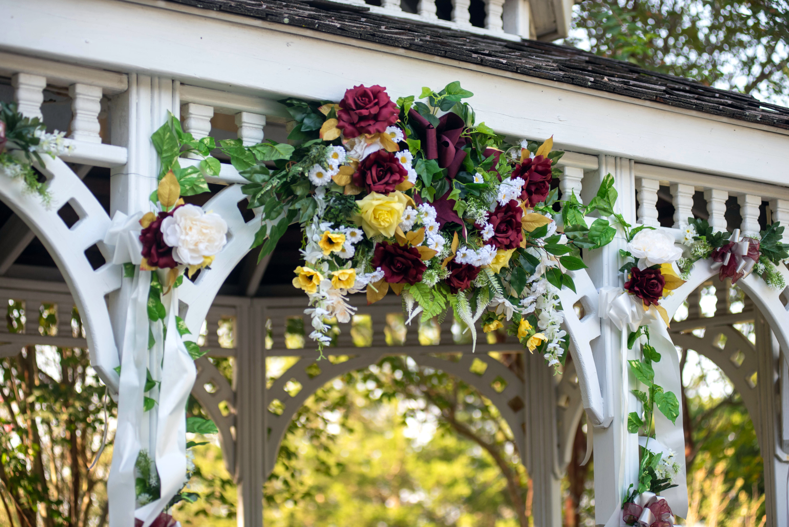 Red and white Rose arrangement on a gazebo overhang in the afternoon - Covid-19 Weddings