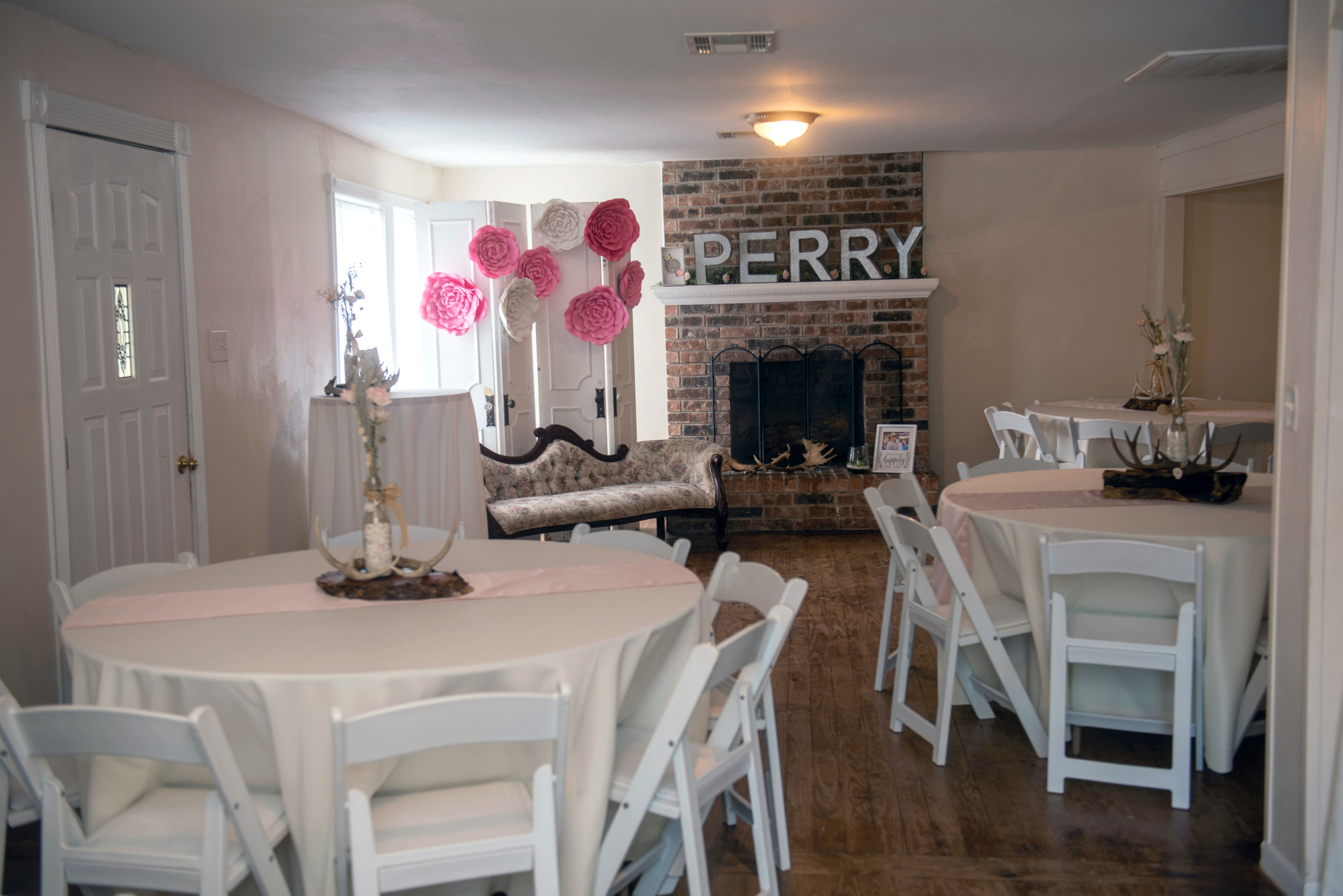 event setup for a bridal shower with white linens and pink balloons in a window - Covid-19 Weddings