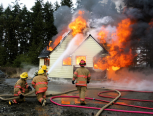 """ALT=""""homeowner's accident liability in a burning house being extinguished by firefighters, blog post image for Insurance Problem Solver and Luke Brown"""""""