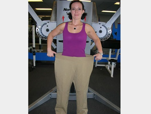 a front view photo of smiling female transformation client wearing her former pants to show how much weight she has lost